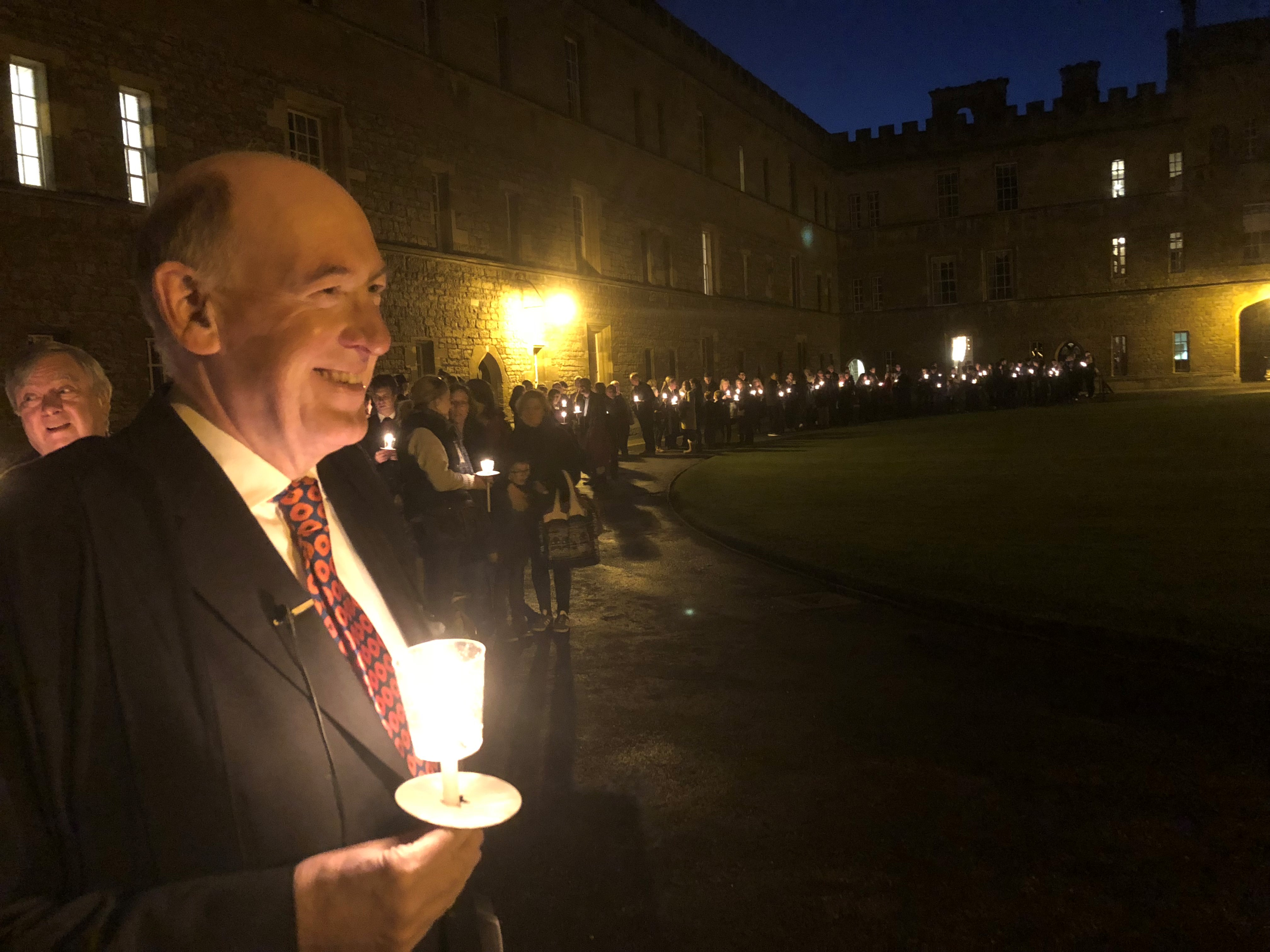 Warden leading candlelit procession through Great Quad