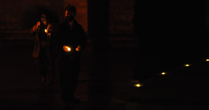 Two students in masks preparing to place their tea lights